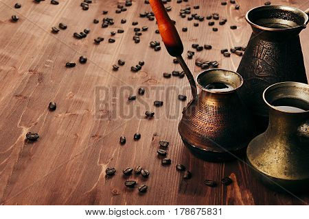 Hot coffee in group shabby antique turkish pots cezve with crema beans with blur on brown old wooden board background. Rustic style.