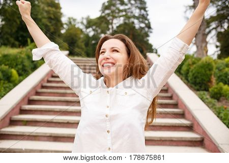 Happy woman with raised hands standing near stairs in park. Hispanic girl looking excited