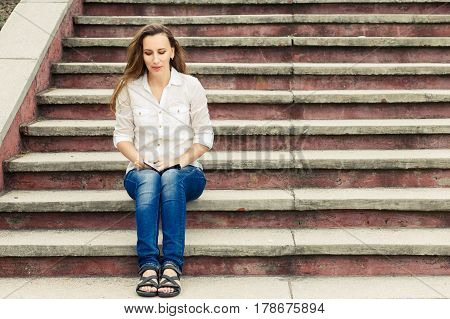 Young caucasian girl sitting on stairs with notebook. Thoughtful woman portrait with copy space aside