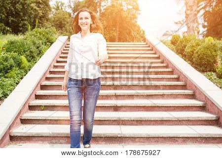 Happy young woman in white shirt going down the stairs in park