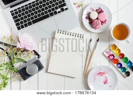 Feminine flat lay workspace with watercolor paintbrushes laptop cup of tea photo camera and flowers on white wooden table. Top view mock up.