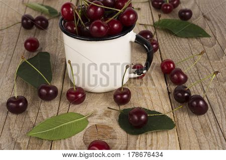 Background of ripe cherries. Pile of fresh and tasty cherries in emal cup. Fresh cherries scattered on a wooden table. Top view.