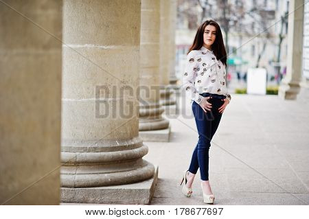 Young Stylish Brunette Girl On Shirt, Pants And High Heels Shoes, Posed Near Stone Columns. Street F
