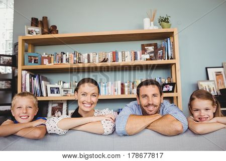 Portrait of happy family with arms crossed behind sofa in house