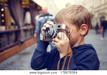 Cute boy holding old film camera and taking a photograph on the street. Warm color toned image