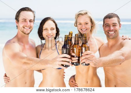 Portrait of happy friends toasting beer bottles on the beach on a sunny day