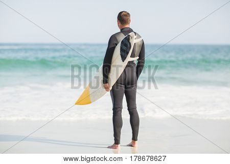 Surfer with surfboard standing on the beach on a sunny day