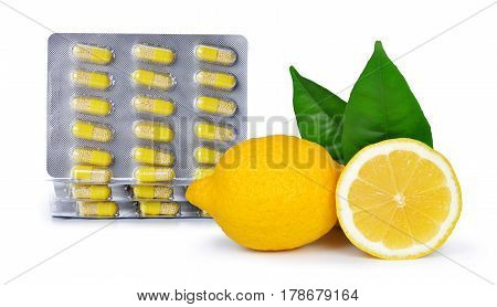 Yellow capsule pills with lemons isolated on white background