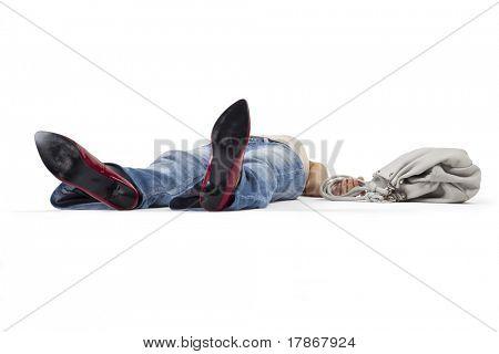 Woman in a faint lying on the floor holding a bag.