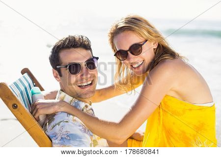 Portrait of young couple sitting on arm chair and embracing on the beach
