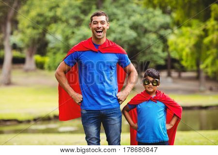 Father and son in superhero costume standing in park