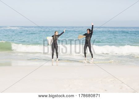 Couple with surfboard standing on the beach on a sunny day