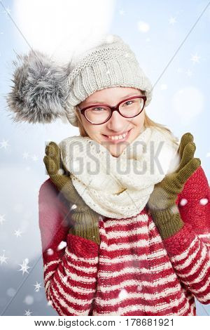 Smiling young woman with glasses in the snow in winter