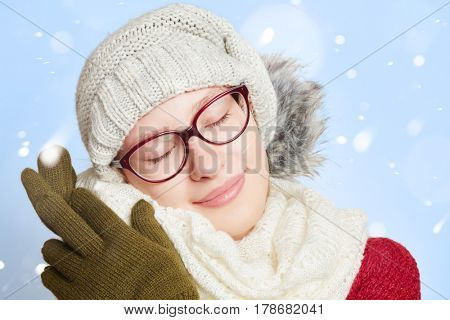 Sleeping young woman in the snow in winter wearing winter clothing
