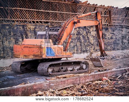 Excavator At Demolition Site Breaking Down The Building