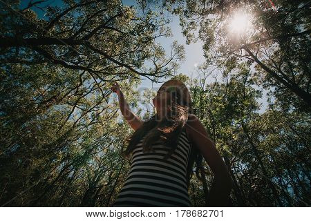 Woman pointing to the trees in an eucalyptus forest in Australia.