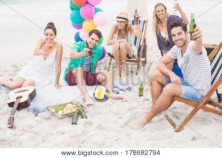 Group of friends toasting beer bottles on the beach on a sunny day