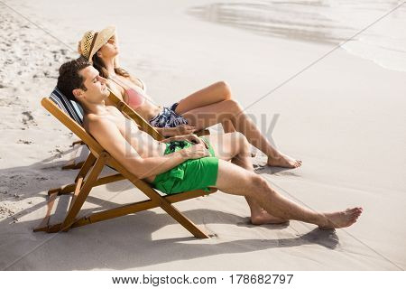 Young couple relaxing on armchair on the beach at a sunny day