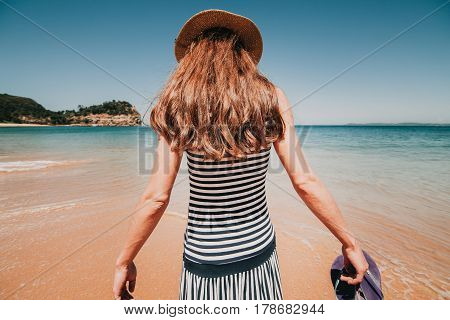 Woman in her back entering into a beautiful Australian beach.