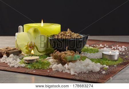 Spa accessories with soap orchid flower bowl with dried chamomile flowers bottles with aromatic oil sea salt candles on bamboo napkin