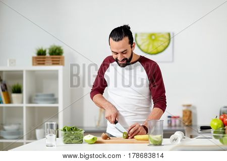 healthy eating, vegetarian food, diet and people concept - happy young man with blender and fruits cooking at home kitchen