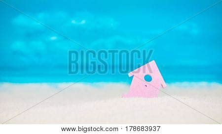 Symbol of little lilac house on the sand with bright cloudy blue painted sky background.