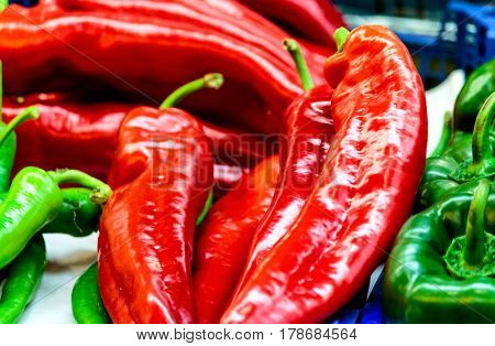 Red and green peppers display at market stall