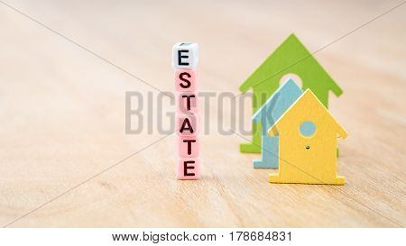 ESTATE word of cube letters behind coloured house symbols on wooden surface. Concept.