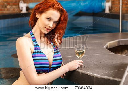 Red-haired Girl Relaxing At Swimming Pool, Enjoying The Water.