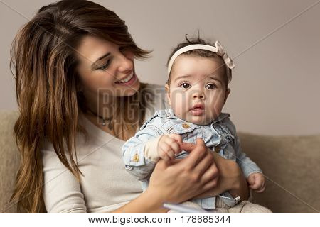 Young mother holding her baby girl in her lap playing and enjoying motherhood. Focus on the baby
