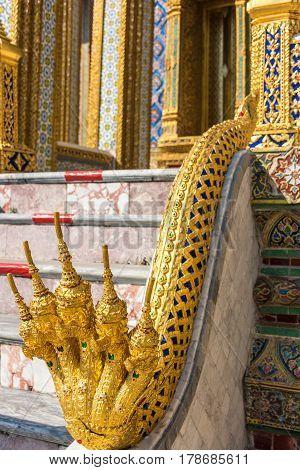 Golden Naga serpent decoration of handrail in Grand Palace. Bangkok Thailand