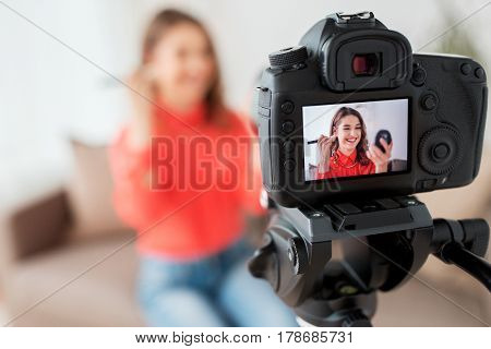 blogging, technology, videoblog and people concept - happy smiling woman or beauty blogger with bronzer, brush and camera recording makeup tutorial video at home