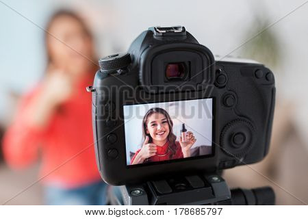 blogging, technology, videoblog, makeup and people concept - happy smiling woman or beauty blogger with foundation and camera recording tutorial video at home and showing thumbs up