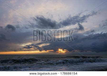 The raging black sea on the background of sunset