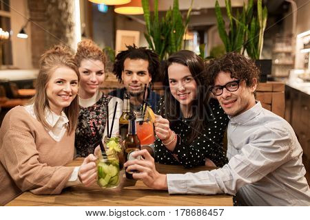 leisure, party, people and holidays concept - happy friends clinking drinks at bar or cafe