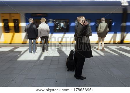 utrecht netherlands 15 march 2017: man makes phone call on platform of new central railway station in utrecht while train arrives