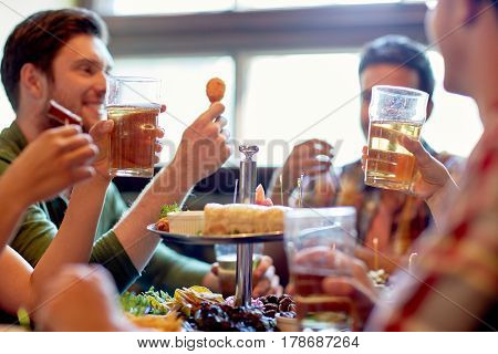 leisure, food, drinks, people and holidays concept - happy friends eating and drinking at bar or pub