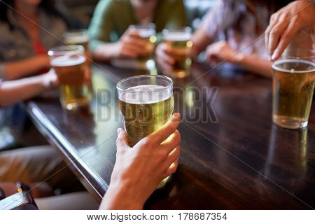 people, leisure and drinks concept - friends drinking beer and at bar or pub