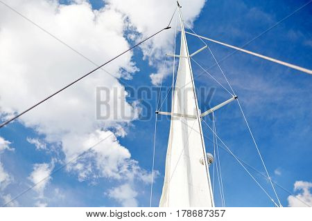 travel, yachting and sailing concept - white sail on mast of boat over blue sky