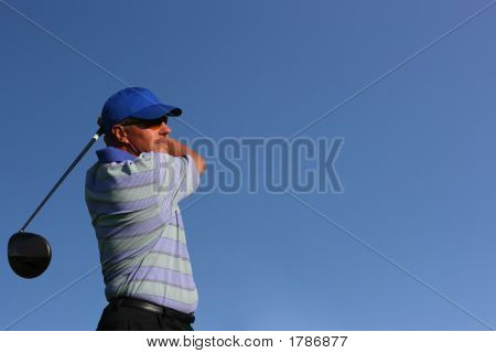 Close Up Of Golfer Teeing Off On Isolated Blue Background With Copy Space
