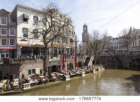 utrecht netherlands 15 march 2017: people enjoy sunny day in early spring on open air cafe at oude gracht in utrecht with Dom tower in the background