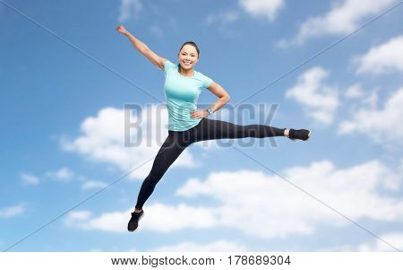 sport, fitness, motion and people concept - happy smiling young woman jumping in air over blue sky background
