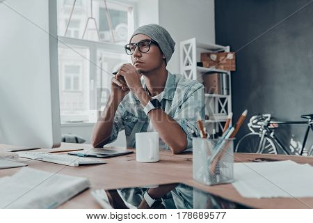Thinking about every detail. Handsome young man looking at computer monitor while sitting at his working place in creative office