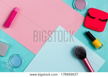 Beauty products, everyday make-up. Cosmetic essentials - eyelashes, eyeshadow, lipstick and nail polish on bright background, flat lay, top view
