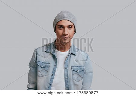 He got great style. Good looking young man in jeans shirt and headwear looking at camera with smile while standing against grey background