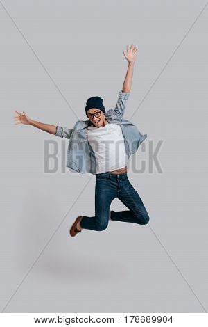 Man in mid-air. Full length of handsome young man in jeans shirt keeping arms outstretched and looking at camera with smile while jumping against grey background