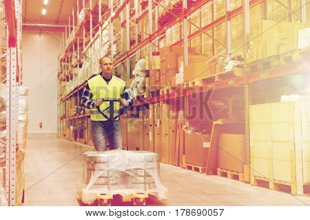 wholesale, logistic, loading, shipment and people concept - man carrying loader with goods at warehouse