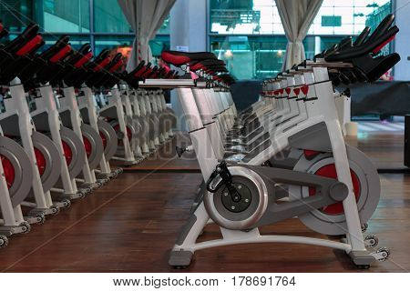 Fitness Workout in Gym: Group of Modern Spinning Bikes in Line