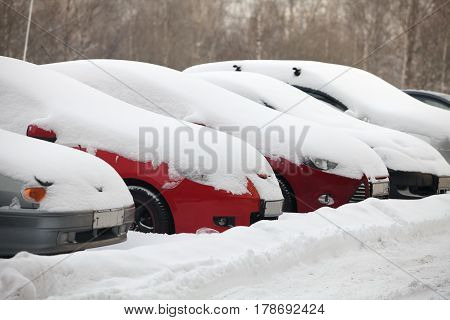 Parking row of cars covered with snow on road big snowdrifts snow storm Cold winter