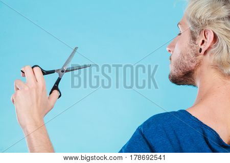 Coiffure hairstyle and haircut. Young cool guy holding special shears tool for work of hairdresser on blue